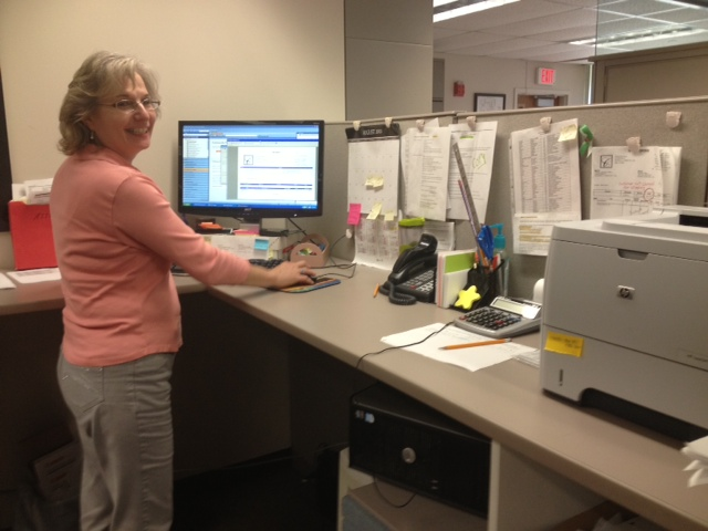 Margie standing at her desk at work