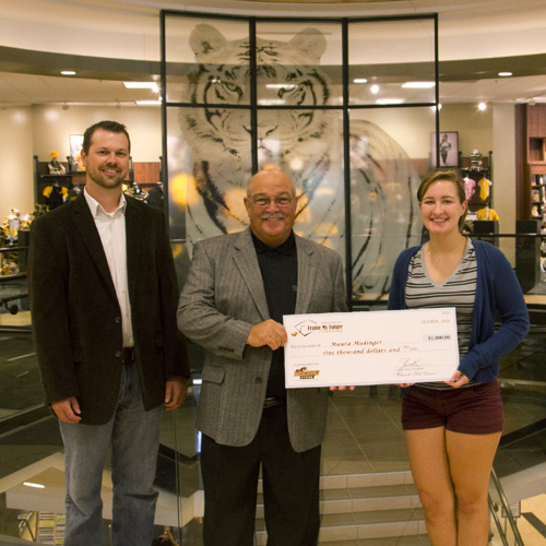 Maura Madinger - Winner of Frame My Future holding her scholarship check at The Mizzou Store