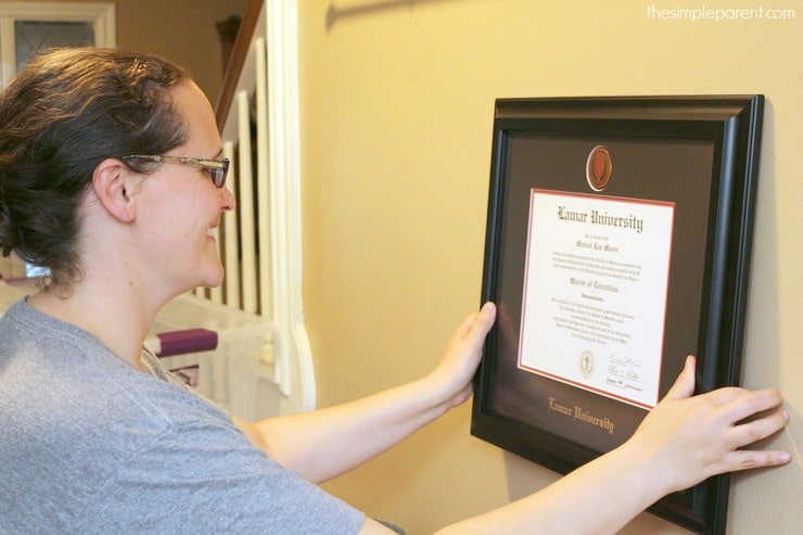 woman hanging lamar diploma frame by church hill classics
