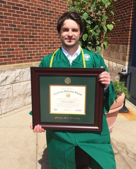 recent graduate holding diploma frame from church hill classics