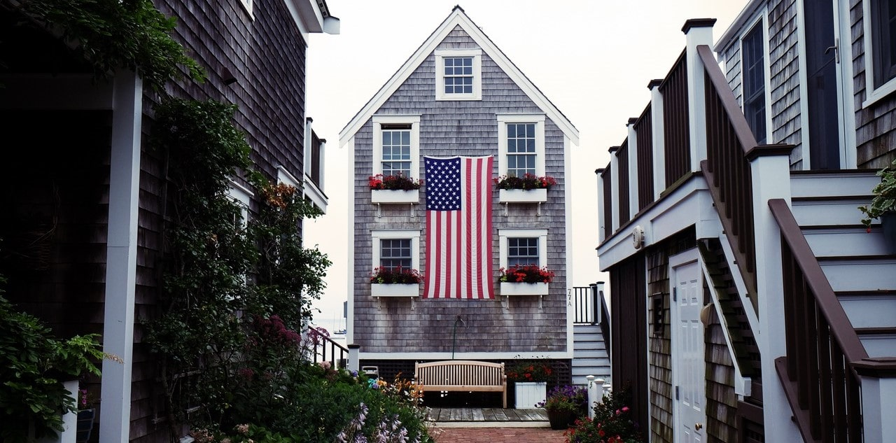 american-flag-hanging-between-bench-flowers-house