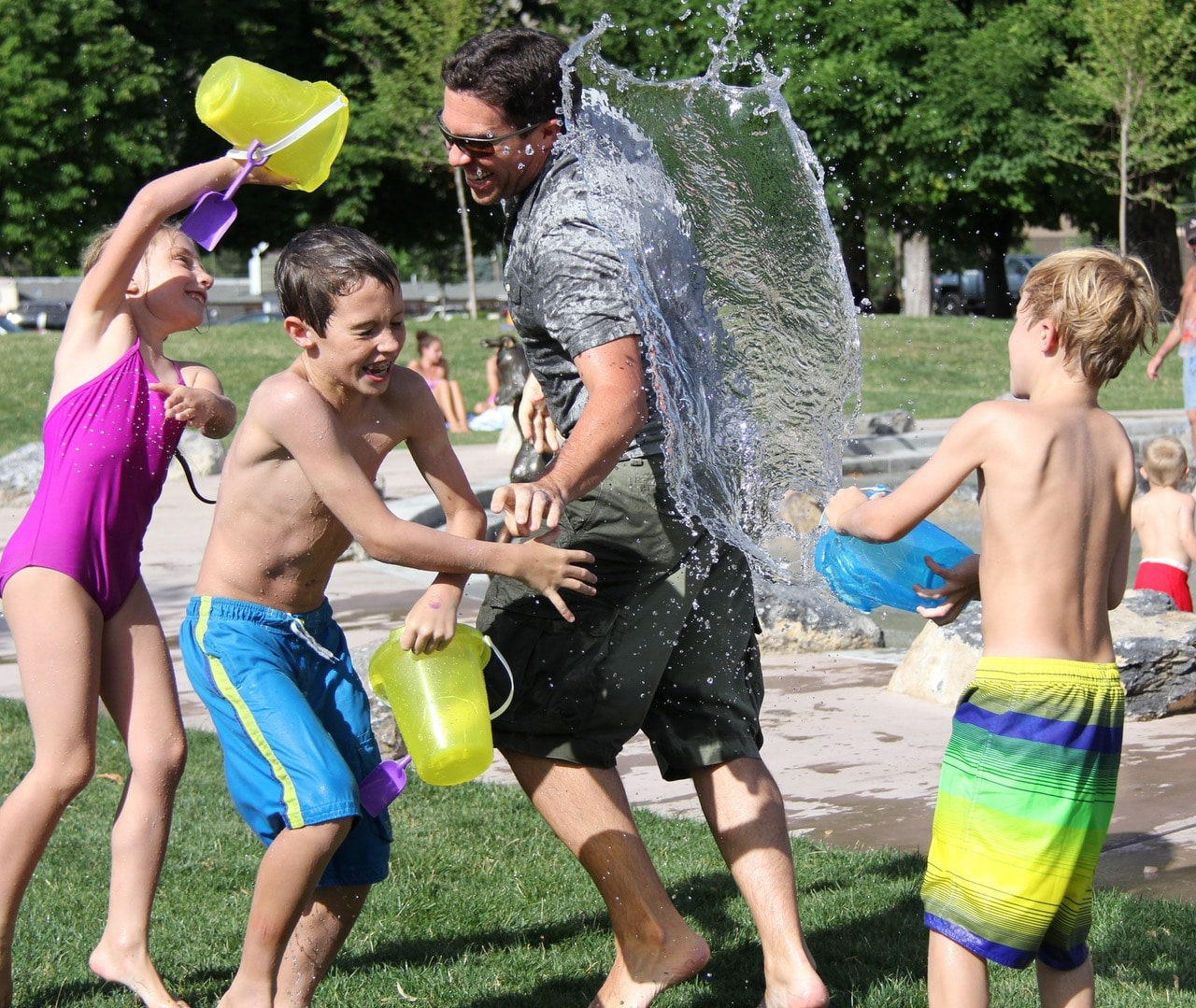 father-having-water-fight-with-children